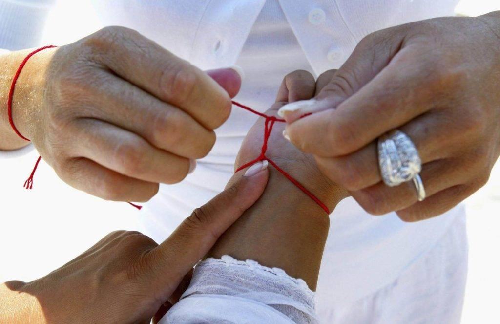 Красная нить: значение оберега, как правильно завязать и на какой руке носить